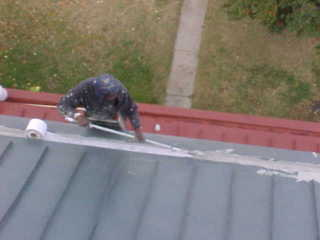 Roof Menders crew member embedding mesh into base acrylic